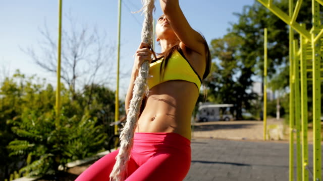 sportswoman climb on a rope outdoor - reggiseno sportivo video stock e b–roll
