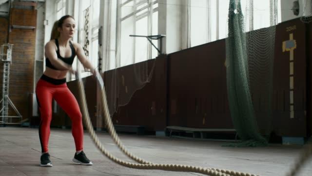 Bидео Sportswoman Doing Battle Rope Workout