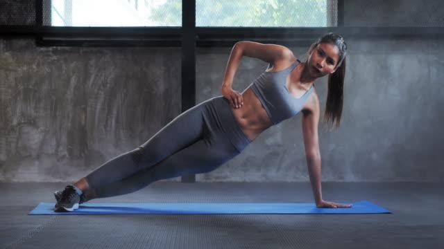 sportswoman doing sit ups in gym.bodybuilding gym training routine.women in sport - rozciągać filmów i materiałów b-roll