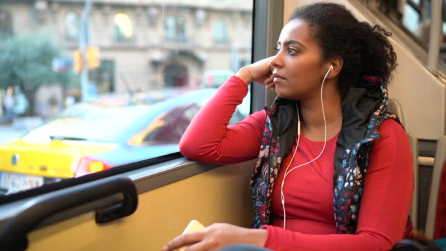 Sportswoman in the bus Sportswoman travelling in bus and looking through the window thinking stock videos & royalty-free footage