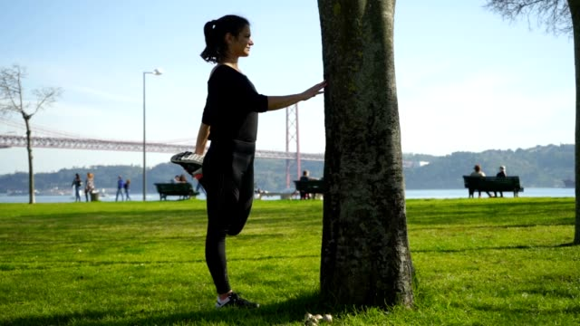 Sportswoman leaning at tree and stretching leg Sportswoman leaning at tree and stretching leg. Side view of beautiful athletic girl in sportswear stretching and training in park. Working out concept leaning stock videos & royalty-free footage