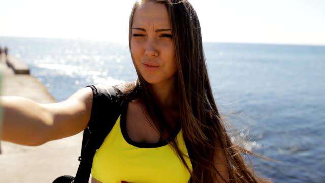 sportswoman make a selfie at sea background - спортивный бюстгальтер стоковые видео и кадры b-roll