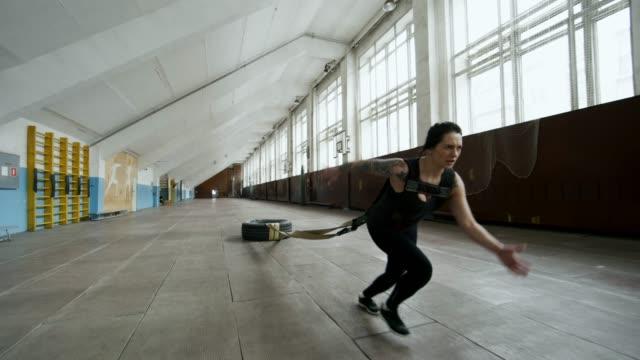 スポーツウーマン実行と重いタイヤを引っ張る - 重い点の映像素材/bロール