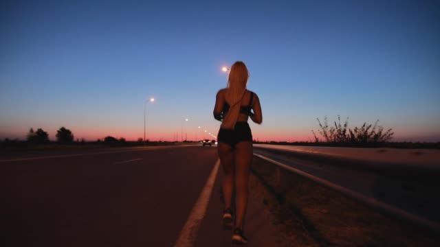 vidéos et rushes de sportive fonctionnant à la route de nuit - joggeuse