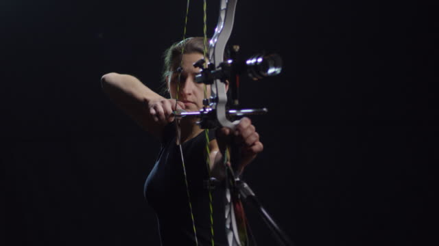 vidéos et rushes de sportive tir flèche sur fond noir - tir à l'arc