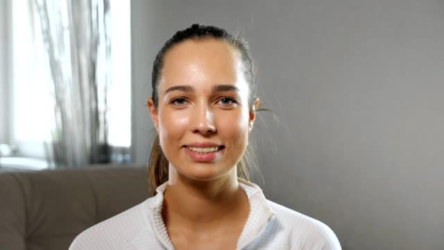 vídeos y material grabado en eventos de stock de deportista sonríe posando para la cámara en la habitación espaciosa luz - sudadera