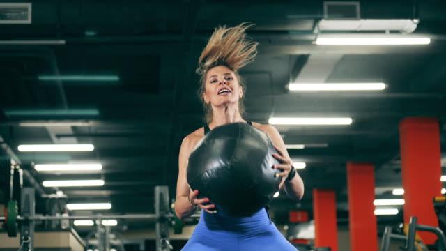 sportlerin hockt mit einem ball im fitnessstudio. - menschliches gelenk stock-videos und b-roll-filmmaterial
