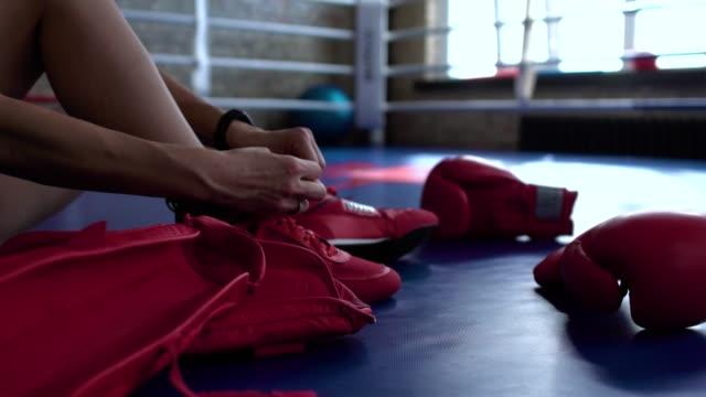 スポーツウーマンはボクシングのリングでの戦いの前に靴ひもを結ぶ - 結ぶ点の映像素材/bロール