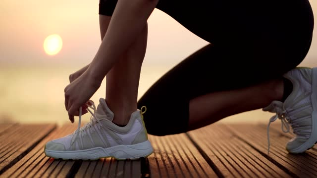 Sportswoman tying shoelace Young woman is tying shoelace and jogging at sunset by the sea. shoe stock videos & royalty-free footage