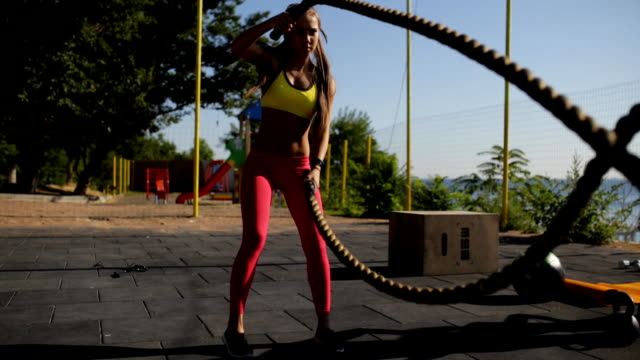 sportswoman workout outdoor. cross-training exercise with rope. - reggiseno sportivo video stock e b–roll