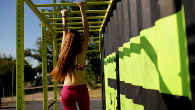 sportswoman workout outdoor. she climb on the crossbars. - reggiseno sportivo video stock e b–roll