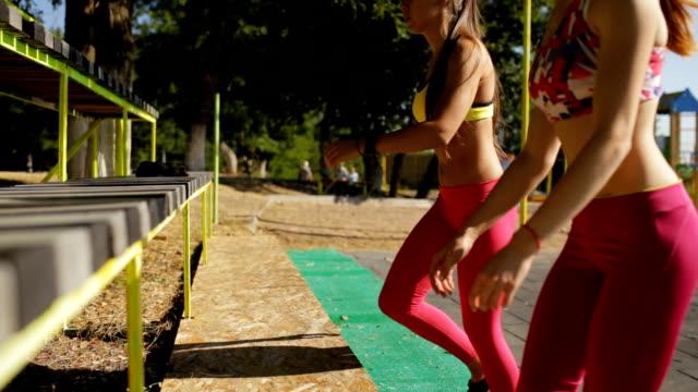 sportswomen doing gym exercise on sports ground - спортивный бюстгальтер стоковые видео и кадры b-roll