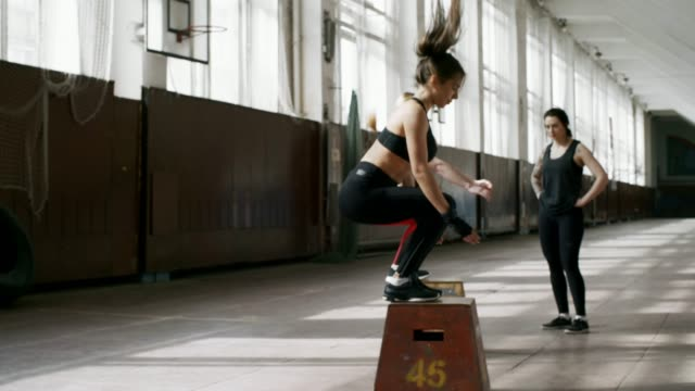 Sportswomen Doing Plyometric Exercise PAN of strong sportswomen jumping on boxes while doing plyometric exercise during cross-training workout cross training stock videos & royalty-free footage