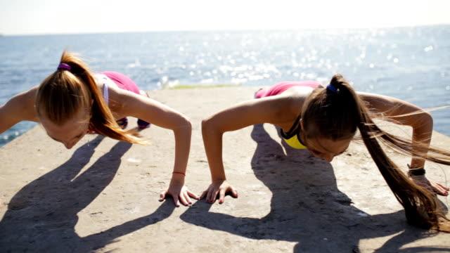 sportswomen push ups outdoor on sea pier - спортивный бюстгальтер стоковые видео и кадры b-roll