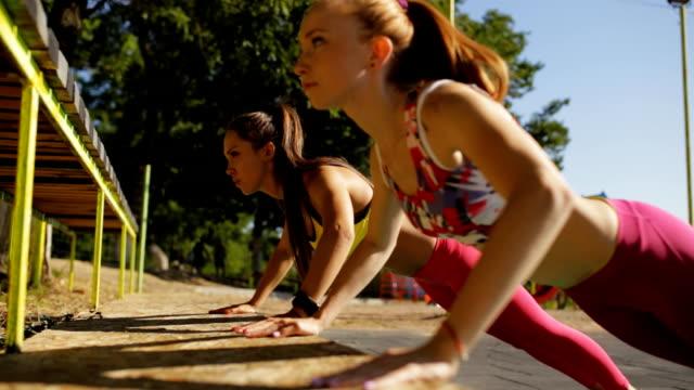 sportswomen push ups outdoor on sports ground - спортивный бюстгальтер стоковые видео и кадры b-roll