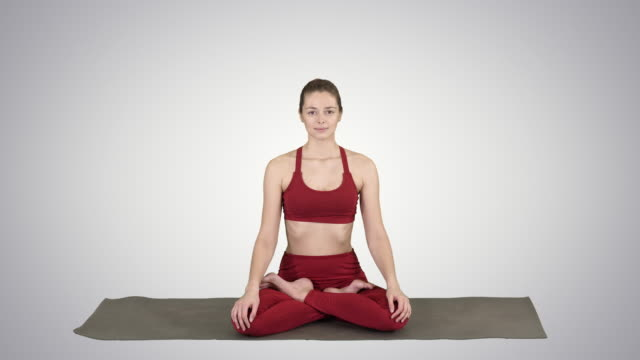 sporty attractive woman practicing yoga, sitting in lotus exercise, siddhasana pose breathing on gradient background - mudra video stock e b–roll