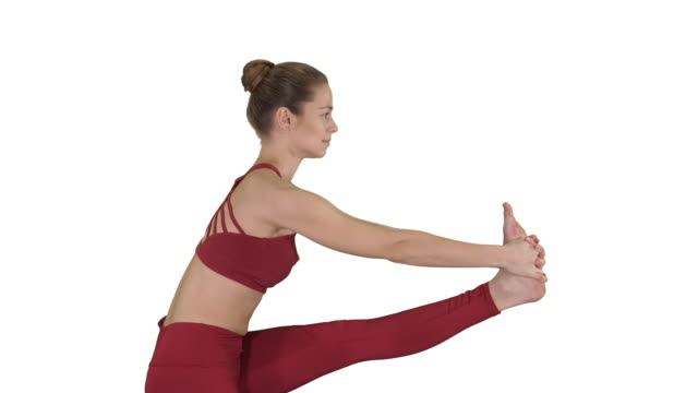 Sporty beautiful blond young woman in sportswear doing Utthita Hasta Padangushthasana on white background