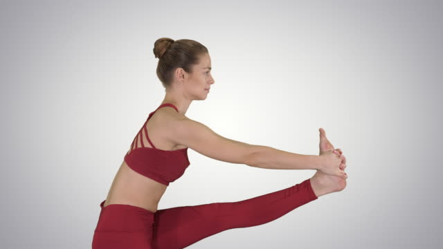 Sporty beautiful blond young woman in sportswear doing Utthita Hasta Padangushthasana on gradient background