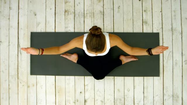 スポーティな美しい若い女性ヨガの練習、十字の脚の位置に座っています。 ビデオ