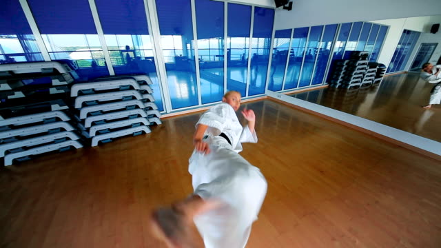 sportliche blonde trainingskarate-tricks im fitnessstudio - karate stock-videos und b-roll-filmmaterial