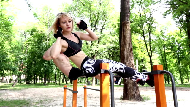sporty blonde young woman and bearded man pumping abdominal muscles in a park outdoor. - donna forzuta video stock e b–roll