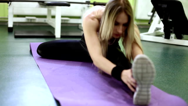 sporty blonde young woman warming up before training in a  gym. - donna forzuta video stock e b–roll