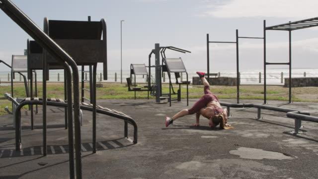 sporty caucasian woman exercising in an outdoor gym during daytime - ludzka kończyna filmów i materiałów b-roll