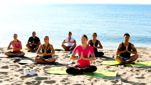 sporty females and males meditating in yoga position - gambe incrociate video stock e b–roll