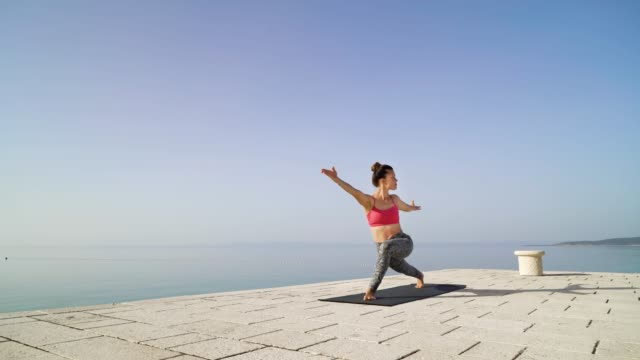 Sporty fit girl practicing yoga on sea pier