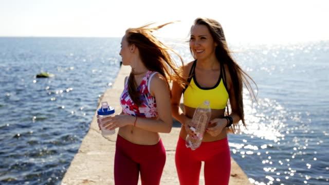 sporty girlfriends drink water on sea pier after workout training - спортивный бюстгальтер стоковые видео и кадры b-roll