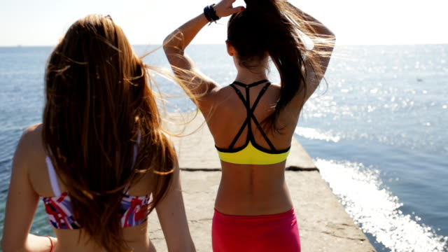 sporty girlfriends go on sea pier, back view. - спортивный бюстгальтер стоковые видео и кадры b-roll