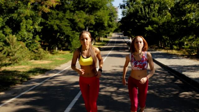 sporty girlfriends jogging together outdoor in park - спортивный бюстгальтер стоковые видео и кадры b-roll