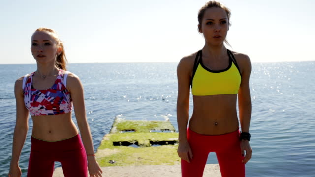 sporty girlfriends jumping on sea pier. workout training. - спортивный бюстгальтер стоковые видео и кадры b-roll