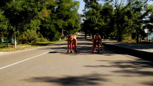 sporty girlfriends low start running outdoor in park - спортивный бюстгальтер стоковые видео и кадры b-roll