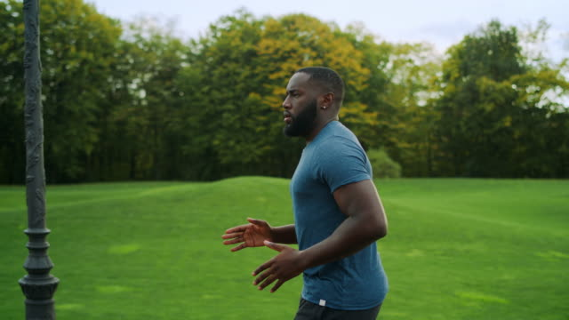 Sporty man jogging in green park. Runner doing cardio workout on road Side view sporty man jogging in green park. Handsome sportsperson exercising outdoors in slow motion. Male runner doing cardio workout on road in morning. African man running outdoors beard stock videos & royalty-free footage