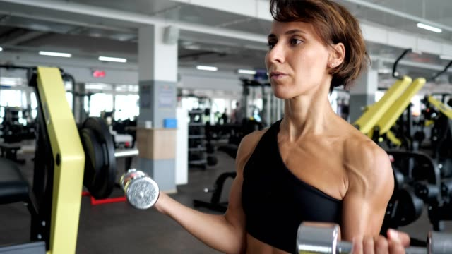 Sporty mature woman is making biceps exercise with dumbbells in gym.
