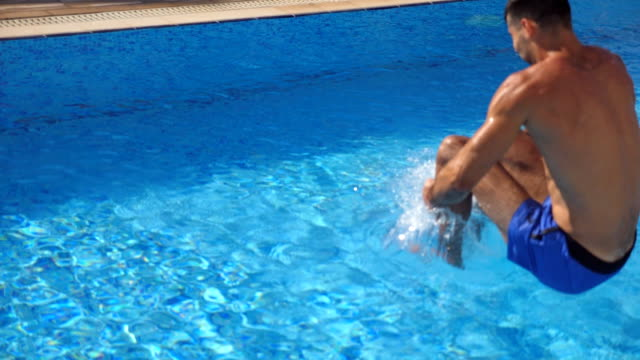vídeos de stock e filmes b-roll de sporty muscular man jumping in water of basin on sunny day. young guy swimming in pool. summer vacation or holiday concept. close up slow motion rear back view - água parada