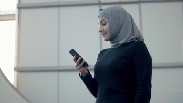 sportig muslimska fitness kvinna i hijab använder smart telefon (slow motion) - hijab bildbanksvideor och videomaterial från bakom kulisserna