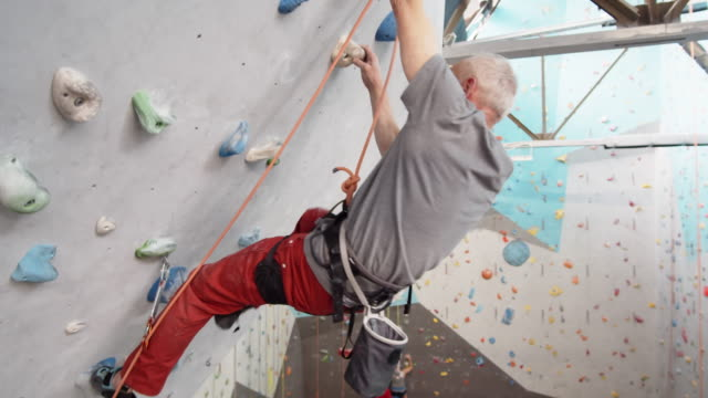 Sporty Senior Practicing Bouldering Indoors