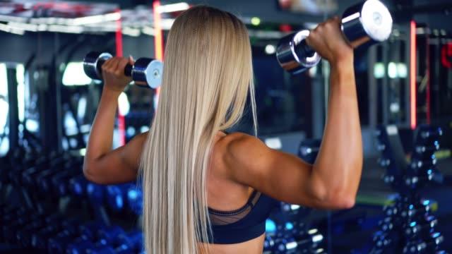 Sporty sportswoman flexing biceps with dumbbells video