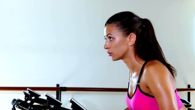 Sporty woman at the gym on bike. Sunny gym video