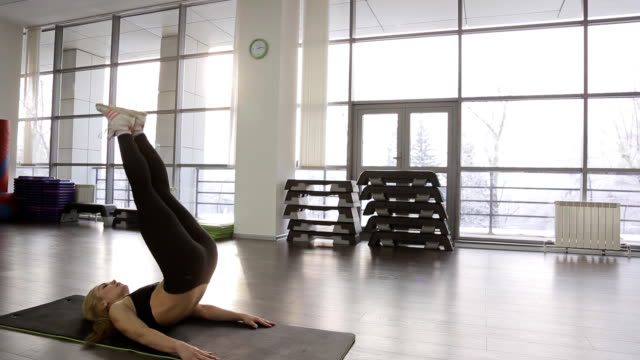 A sporty woman athlete does a workout overall. gymnastics with ankle weights video