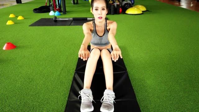 Sporty woman doing abdominal sit-ups or crunches exercise on the floor in gym.