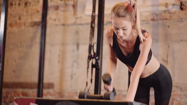 Sporty Woman Doing Back Workout At Health Club