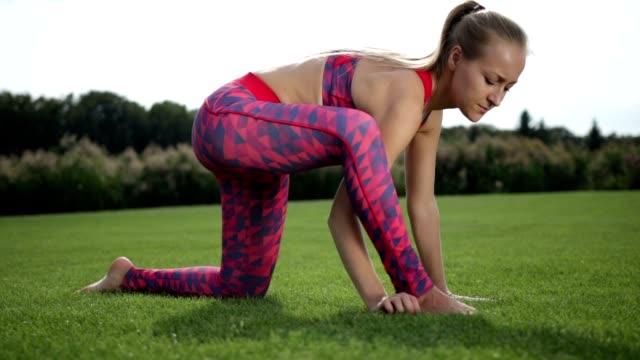 sporty woman doing hip flexor stretch in the park - posizione corretta video stock e b–roll