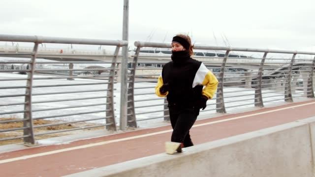 sporty woman jogging on urban bridge in winter - guanto indumento sportivo protettivo video stock e b–roll