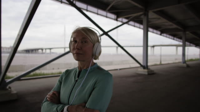 vidéos et rushes de femme sportive écoutant la musique - une seule femme d'âge mûr
