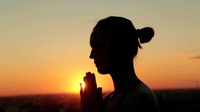 Sporty woman practicing yoga in the park at sunset, making hand greeting namaste video