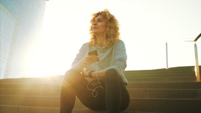 vidéos et rushes de femme sportive se relaxant à l'extérieur. - podcasting