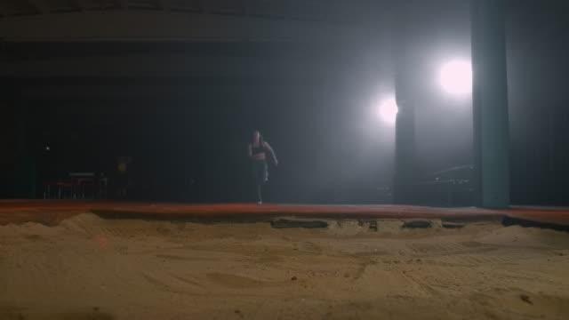 vídeos y material grabado en eventos de stock de una mujer deportiva corre en un estadio y realiza un salto largo en cámara lenta en un estadio sobre un fondo oscuro - largo longitud